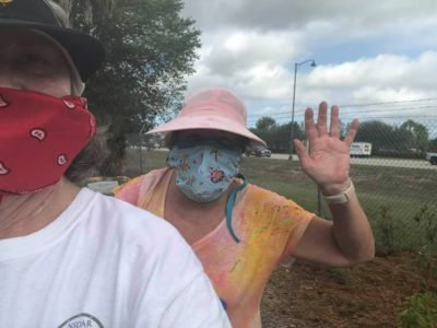 Masked gardeners work on the Butterfly Garden
